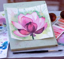 A table with water colour paints and a water colouring painting of a pink flower